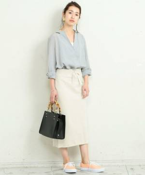 ライトブルーのシャツに白のタイトスカートを履いた女性