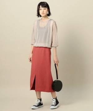 ベージュのニットに赤のタイトスカートを履いた女性