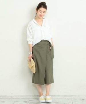 白のブラウスにカーキのタイトスカートを履いた女性