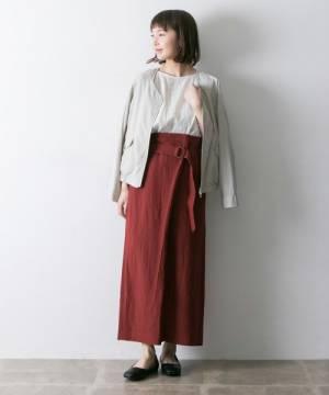 白のレースブラウス、赤のタイトスカートにベージュのジャケットを羽織った女性
