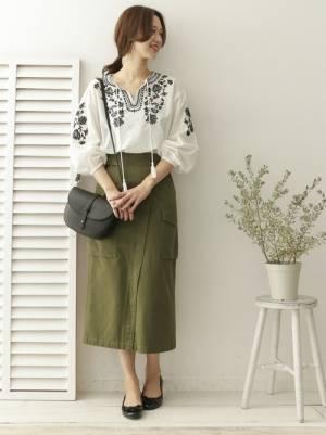 白の刺繍ブラウスにカーキのタイトスカートを履いた女性