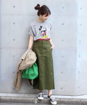 ミッキーTシャツにカーキタイトスカートを履いた女性