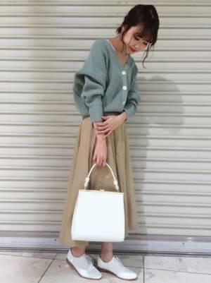 ライトグリーンのカーディガンにベージュのフレアスカートを履いた女性