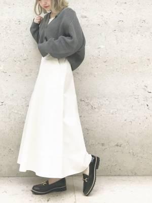 白のレースキャミ、白のフレアスカートにグレーのカーディガンを着た女性
