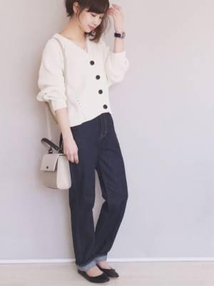 白のカーディガンにデニムパンツを履いた女性