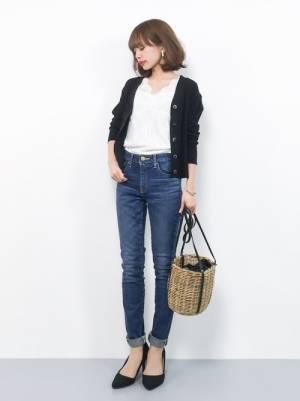白のトップス、デニムパンツに黒のカーディガンを着た女性