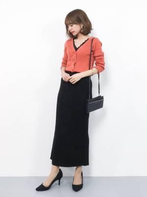 黒のレーストップス、黒のタイトスカートにオレンジのカーディガンを着た女性