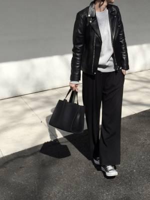 グレーのトップス、黒のワイドパンツにライダースを着た女性