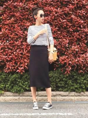 ボーダートップスに黒のタイトスカートを履いた女性