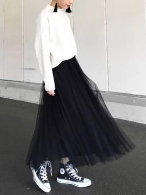 白のセーターに黒のチュールスカートを着た女性