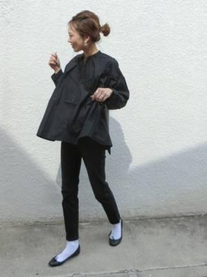 黒のブラウスに黒のパンツを履いた女性