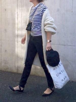 ボーダートップス、黒のスキニーパンツに白のロングカーディガンを着た女性
