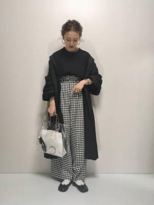 黒のトップス、ギンガムチェックパンツに黒のガウンを羽織った女性