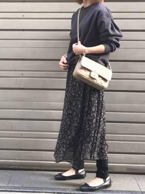 黒のスウェット、黒の花柄スカートを着た女性