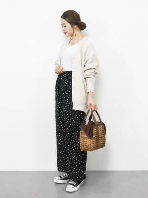 白のトップス、黒のドット柄パンツに白のカーディガンを着た女性