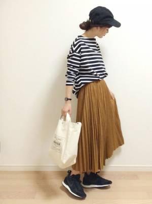 ボーダートップスにスカートを合わせてトートバッグを持った女性