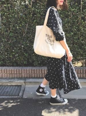 ドットのワンピースに黒いスニーカーを履いてトートバッグを持った女性