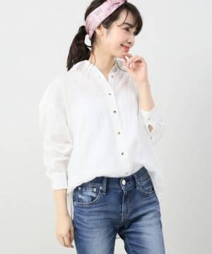 白のリネンシャツにデニムを合わせた女性