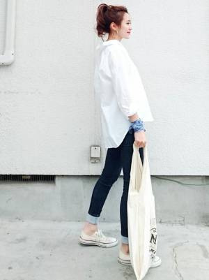 たっぷりとした白シャツにスキニーデニムを合わせた女性
