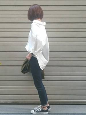 スキニーデニムに白シャツをフロントインした女性