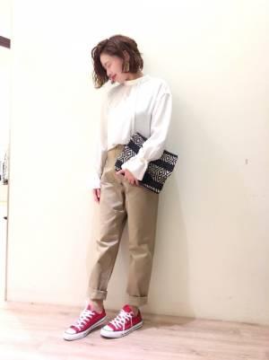 白ブラウスにベイカーパンツを合わせて赤いスニーカーを履いた女性
