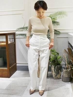 ベージュのトップスに白いベイカーパンツを合わせてベージュのパンプスを履いた女性