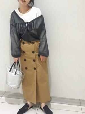 白いTシャツにチノスカートを合わせてクリアバッグを持った女性