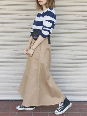 ボーダートップスにチノスカートを合わせて黒いスニーカーを履いた女性