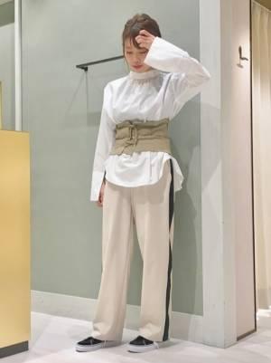 白シャツとビスチェにラインパンツを履いた女性