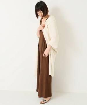 ブラウンのサロペットに白のロングカーディガンを着た女性