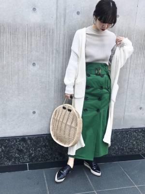 ベージュのトップス、グリーンのトレンチスカートに白のロングカーディガンを着た女性