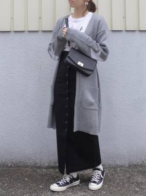 白のTシャツ、黒のロングスカートにグレーのロングカーディガンを着た女性