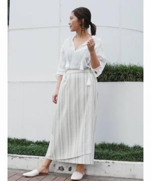 白のブラウスにストライプ柄ラップスカートを履いた女性