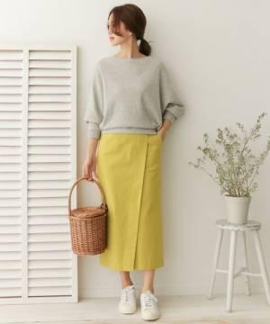 グレーのスウェットに黄色のラップスカートを履いた女性
