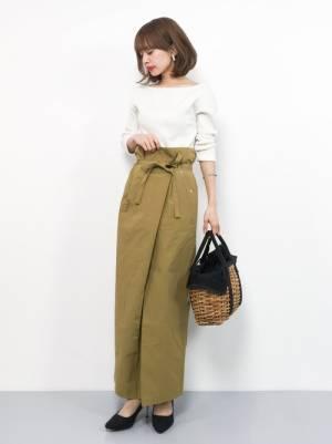 白のトップスにベージュのラップスカートを履いた女性
