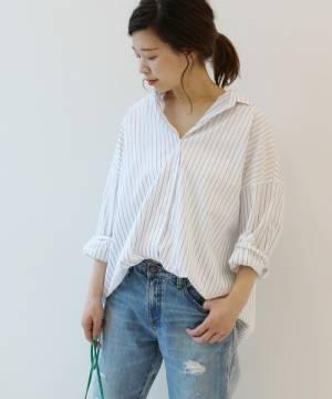 白のストライプシャツにデニムパンツを履いた女性