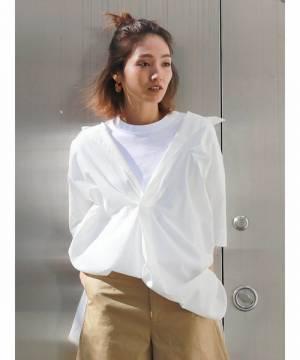 白Tシャツに白シャツ、ベージュパンツを履いた女性