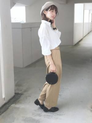 白シャツにベージュのチノパン、ベレー帽を被った女性