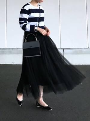 ネイビー×白の太ボーダーに黒のチュールスカートを合わせた女性