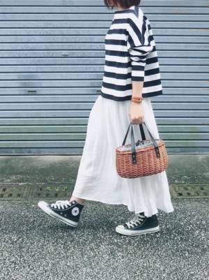 ネイビー×白の太ボーダートップスに白のフレアスカートを合わせた女性