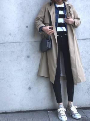 黒×白のボーダーTシャツに黒スキニーを合わせて、デニムジャケットとトレンチコートを羽織った女性