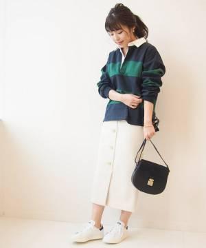 ラガーシャツにフロントボタンスカートを合わせた女性
