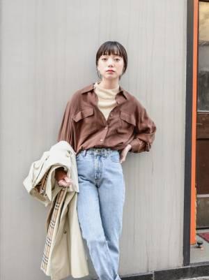 ニットにシャツをレイヤードしてデニムパンツを履いた女性