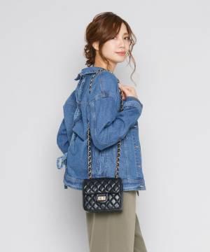 チェーンのショルダーミニバッグを掛けた女性