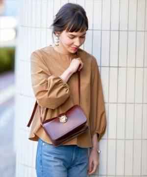 赤いレザー調のミニショルダーバッグを掛けた女性