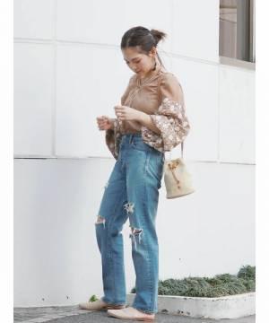 ボリュームスリーブに刺繍がほどこされたベージュのブラウスにデニムパンツを合わせた女性