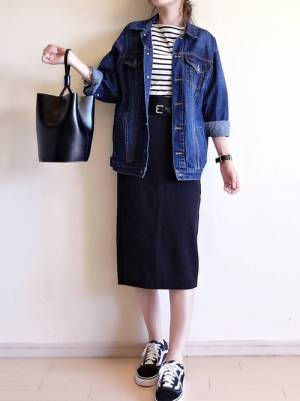 ボーダートップス、黒のタイトスカートにGジャンを着た女性