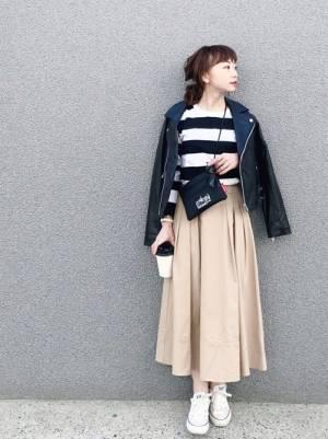 ボーダートップス、ベージュのフレアスカートにライダースジャケットを羽織った女性