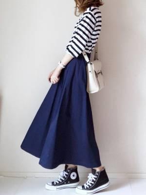 ボーダートップスにネイビーのフレアスカートを履いた女性