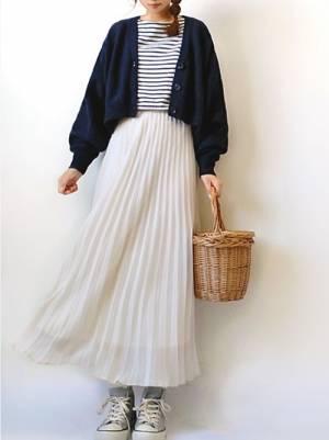 ボーダートップス、白のプリーツスカートにネイビーのカーディガンを着た女性